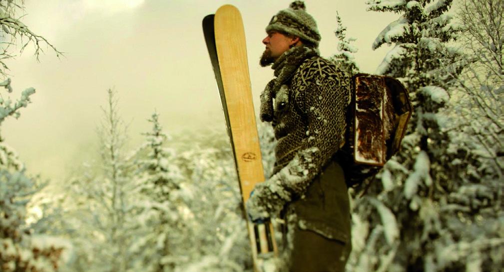 Paire de skis en bois tenue par un homme sous la neige