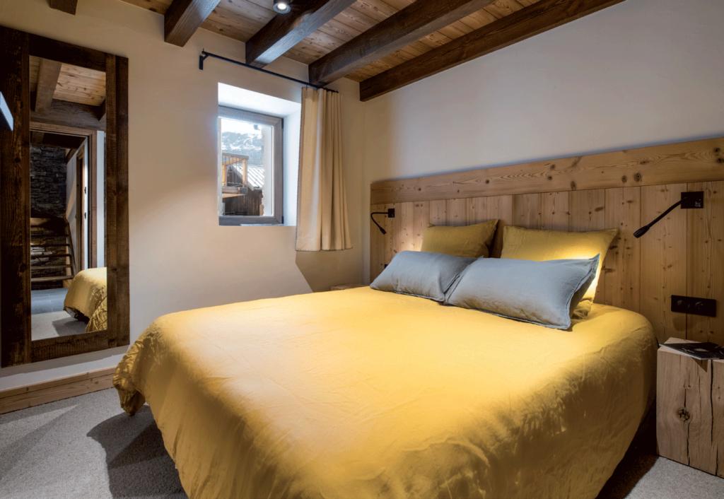chambre-tête-de-lit-en-bois-et-draps-jaunes