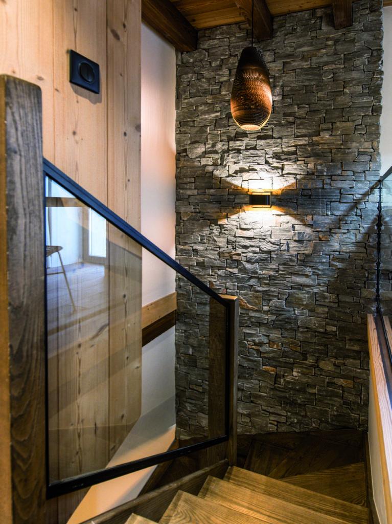 escalier-en-bois-et-mur-de-pierres-avec-luminaires
