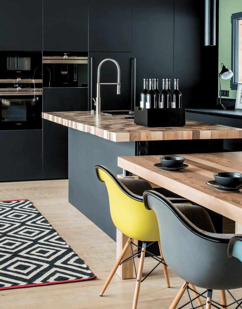 cuisine-noire-avec-plan-de-travail-en-bois-clair-fauteuils-jaune-et-gris