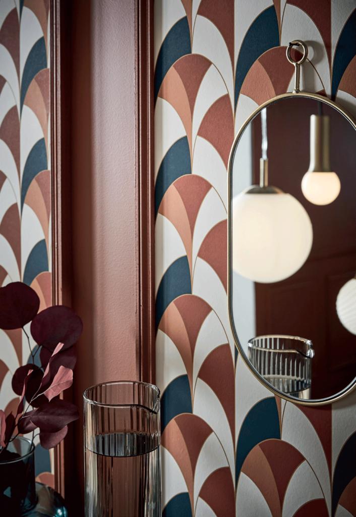 Mur design avec motifs, un miroir avec le reflet de luminaire. Une décoration à la Milanaise.
