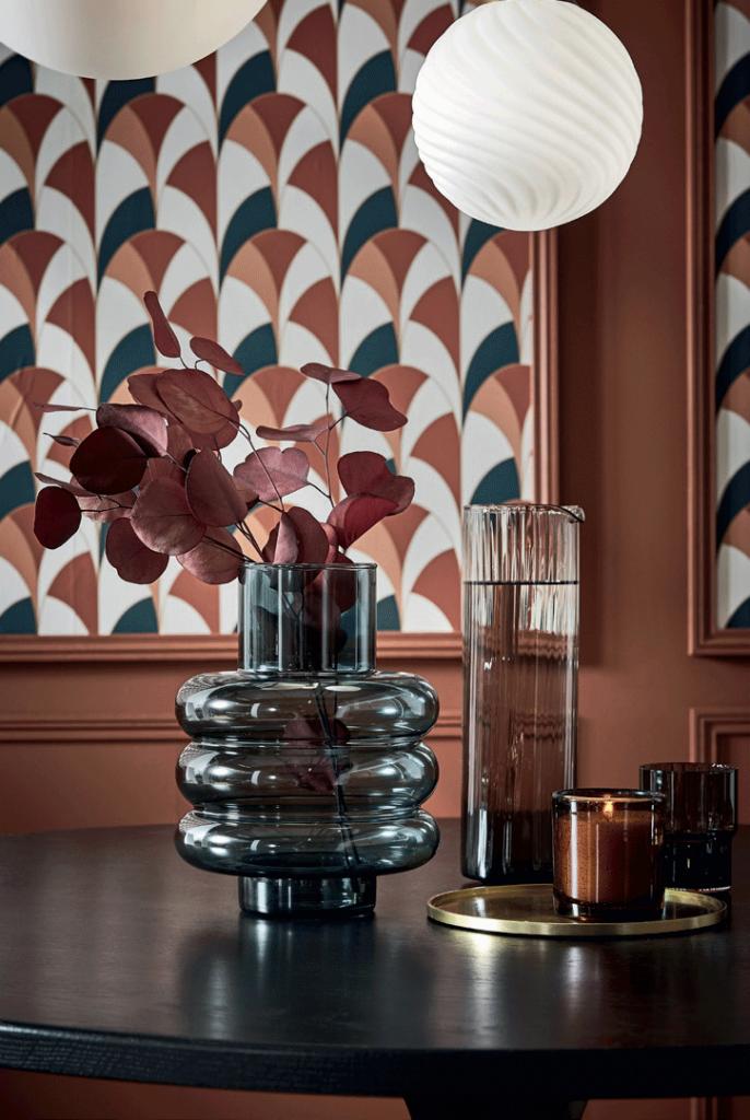 Vase avec fleurs roses, mur à motifs coloré, une décoration design.